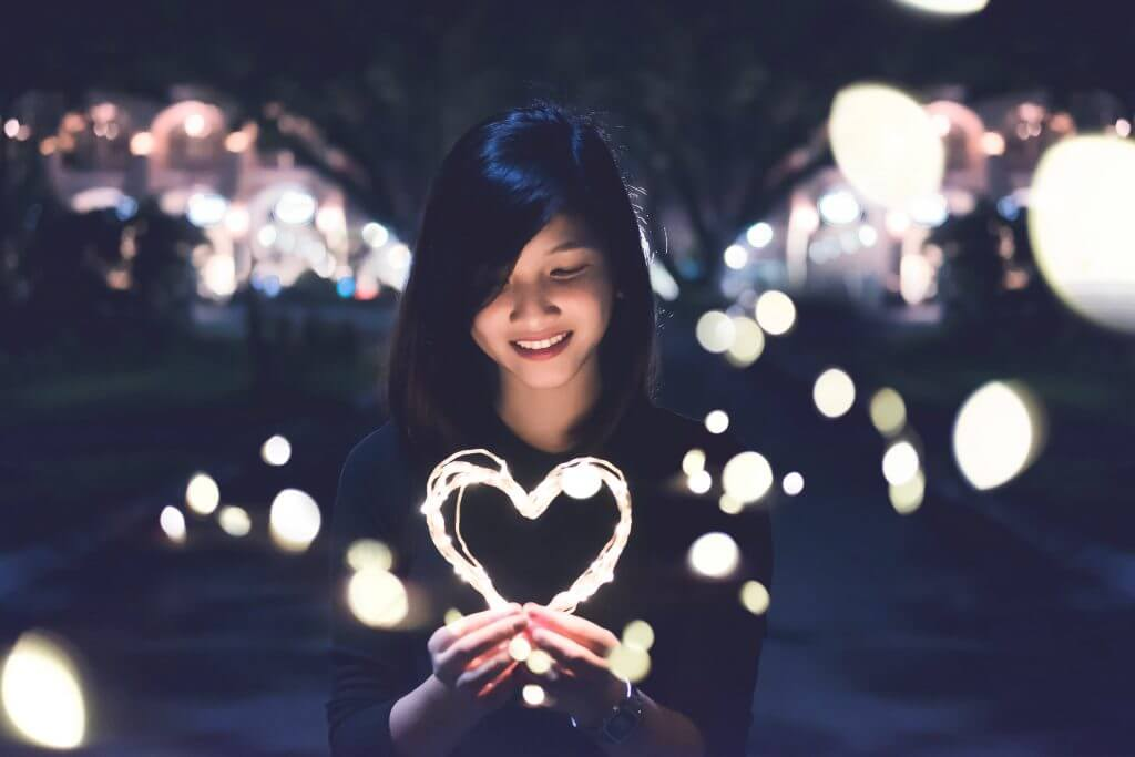 Girl holding a heart of light to symbolise congenital heart disease