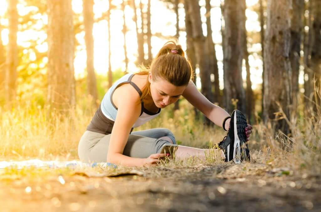 Fit Woman stretching in a forest for exercise and movement