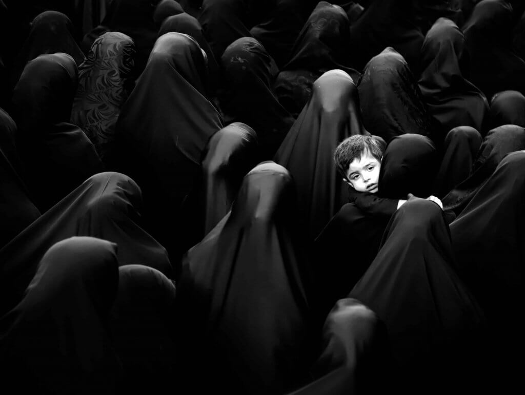 A lone child carried in a sea of black veils
