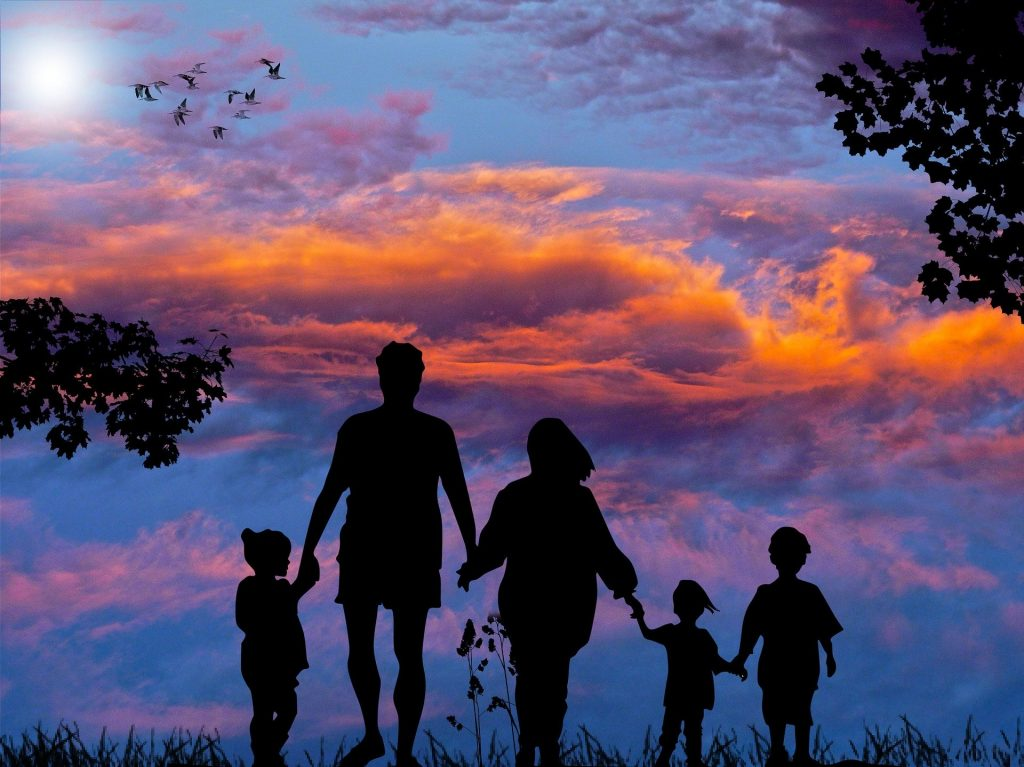 Family linking hands with beautiful sky to signify the importance of connection in nutrition and lifestyle coaching
