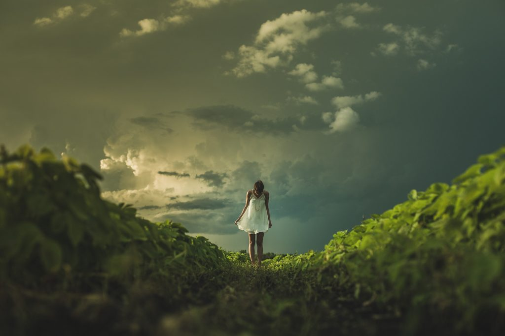 Nutrition and Lifestyle Coaching is like the Light breaking through the clouds behind a girl in a field for stress management