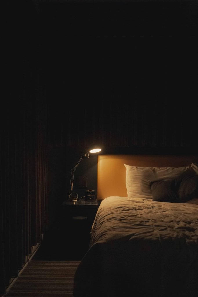 A dark bedroom with reading lamp and radio alarm clock on the bedside table