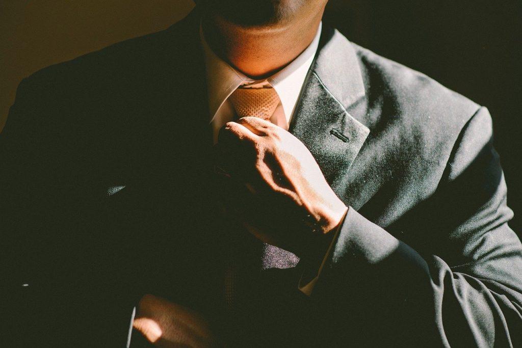 coroporate cult man in suit adjusting his tie